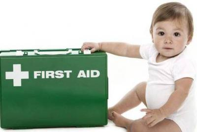 Image of toddler beside a First Aid box