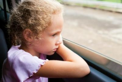 Image of girl looking worried looking out the window